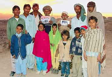 Members of the Hindu Bheel community in Pakistan show pictures of girls who have been kidnapped and converted to Islam